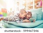 happy siblings lying on sofa at ... | Shutterstock . vector #599467346