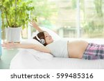 pregnant woman listening to... | Shutterstock . vector #599485316