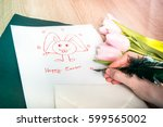 Womans hands drawing original smiling Bunny emoticon, Happy Easter text and little heart with green quill pen on traditional paper letter. Rosy Opalescence pink tulip color of Spring Summer 2017