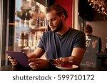 goodlooking young man sitting... | Shutterstock . vector #599710172