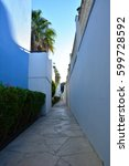 Small photo of Classical Greek architecture at dawn: white and blue wall, palm trees, sun
