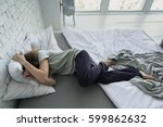 despaired woman lying on bed | Shutterstock . vector #599862632