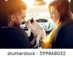 Stock photo cheerful young couple sitting on front seats in car and playing with little puppy 599868032