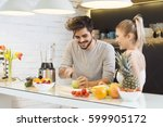 young couple cutting fruit in... | Shutterstock . vector #599905172