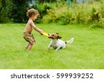Stock photo happy boy playing with dog active game on lawn 599939252