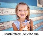 cute little girl is drinking... | Shutterstock . vector #599955506
