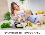 young beautiful mother and her... | Shutterstock . vector #599997752