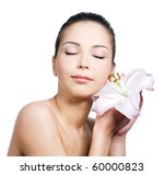 Beauty of young woman with closed eyes holding a lily near the face - isolated on white background - stock photo