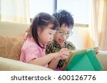 asian siblings playing games on ... | Shutterstock . vector #600126776
