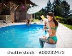 beautiful woman applying uv... | Shutterstock . vector #600232472