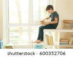 cute schoolboy sitting beside... | Shutterstock . vector #600352706
