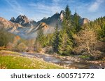 beautiful autumn landscape. composite image of High Tatra ridge. rocky shore of the river in fog that flows near the forest at the foot of the mountain. - stock photo