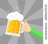 hand holding a mug of beer on a ...   Shutterstock .eps vector #600615515