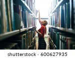 Woman taking book from library...