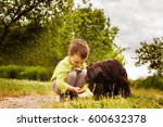 Stock photo boy with a dog walking in the park child playing with the dog 600632378