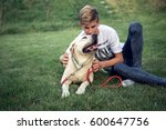 Small photo of Adolescent male with labrador spend time on the grass in the yard