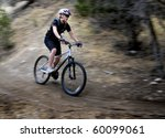 Young Woman Riding Mountain Bike in Wilderness - stock photo