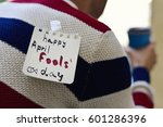 closeup of a young caucasian man seen from behind having a coffee, with a note with the text happy april fools day attached with tape to his back