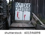 "Door with a sign ""don't open, dead inside"" and bloody handprints visible. The building is a part of zombie hunt decoration for Halloween. - stock photo"