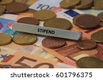 Small photo of stipend - the word was printed on a metal bar. the metal bar was placed on several banknotes