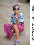 Small photo of Luang Namtha prov., Laos-October 6, 2015: The Akha hill tribe are an ethnic minority living in the mountains between E.Myanmar-N.Thailand-W.Laos-S.China. Pipe-smoking old woman with modern sunglasses.