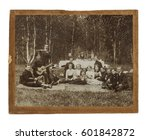 Original antique photo of the early 20th century of a group of seventeen  people at the picnic in Siberia in Russia on the table background with serious granny and samovar with tea.