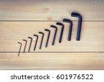 Small photo of Old hex keys are laid out from the smaller to the larger on a wooden background