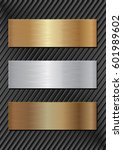 three metal plaques on black...