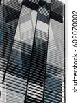 Small photo of Louvered structure. Reworked tilt photo of ajar jalousie / blinds / louvers on large windows. Abstract image on the subject of contemporary architecture.