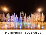 Dancing fountains illuminated at night on square Macedonia in Skopje with famous statue of Alexandeer the Great (worior on horse) at background