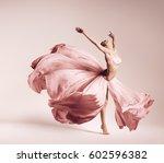 Stock photo ballerina dancing in flowing pink dress in studio 602596382