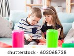 happy siblings sitting on sofa... | Shutterstock . vector #603068738