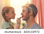 Small photo of dad with cute daughter beeing treated with lipstick for carnival