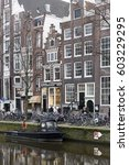 Small photo of Amsterdam, The Netherlands - 18 February 2014: Canal houses along Singel canal with art deco ironmonger store sign, pedestrians, parked bicycles, and moored boat