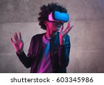 Stock photo cheerful girl with hands up wearing the virtual reality goggles 603345986
