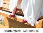 A Brides Red Shoes Rest On The...