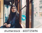 Small photo of Young beautiful eastern woman outdoor in the city smiling looking camera holding smart phone - happiness, customer, technology concept