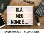 Small photo of Ola, meu nome e ..., Portuguese text for Hello, My Name is..., , vintage style light box on office desktop, high angle birds eye view