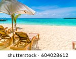 beach chairs with umbrella at... | Shutterstock . vector #604028612