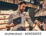 handsome man is choosing a... | Shutterstock . vector #604036055
