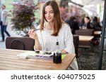 young woman eating sushi... | Shutterstock . vector #604075025