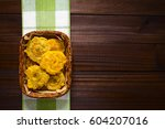 Small photo of Patacon or toston, fried and flattened pieces of green plantains, a traditional snack or accompaniment in the Caribbean, photographed overhead on dark wood with natural light