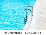 beautiful clear blue water in swimming pool with metal stairs - stock photo