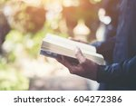 man reading book in his hands. | Shutterstock . vector #604272386