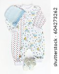 Small photo of newborn baby set of clothes: patterned romper with hat and knitwear booties on white background