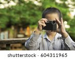Thai boy taking a photo by using small point and shoot camera
