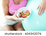 fit woman eating healthy salad... | Shutterstock . vector #604342076