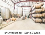 Small photo of Blurred image modern beer plant (brewery) with stainless steel brewing equipments and stack of barrels in cellar. Row large metal tanks in microbrewery. Brewery production vats, fermentation interior.