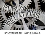 Small photo of Macro photo of tooth wheel mechanism with PUBLIC RELATIONS letters imprinted on metal surface