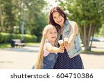 mom and daughter eating ice... | Shutterstock . vector #604710386